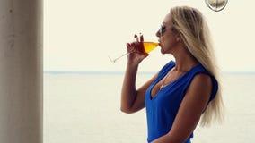 美丽的金发碧眼的女人喝从一个玻璃觚的白葡萄酒,敬佩海洋的天际,站立在游廊 股票视频