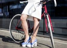 年轻美丽的金发碧眼的女人在有自行车的城市喝 库存照片