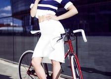年轻美丽的金发碧眼的女人在有自行车的城市喝 图库摄影