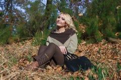 美丽的金发碧眼的女人在秋天坐叶子 库存图片