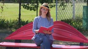 美丽的金发碧眼的女人在长凳的一个公园画在一个册页的一支铅笔 影视素材