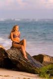 美丽的金发碧眼的女人坐在海洋岸的一个岩石 免版税库存图片