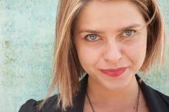 美丽的金发碧眼的女人微笑的凝视的&# 免版税图库摄影