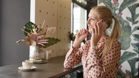 美丽的金发碧眼的女人谈话在咖啡馆的一个手机 微笑智能手机的妇女,讲话在咖啡馆 美丽的年轻女性 影视素材