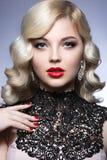 美丽的金发碧眼的女人以与卷毛的好莱坞方式,红色嘴唇和鞋带穿戴 秀丽表面 免版税库存图片