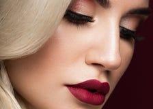 美丽的金发碧眼的女人以与卷毛,红色嘴唇的好莱坞方式 秀丽表面和头发 图库摄影
