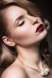 美丽的金发碧眼的女人以与卷毛,红色嘴唇的好莱坞方式 秀丽表面 图库摄影