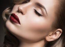 美丽的金发碧眼的女人以与卷毛,红色嘴唇的好莱坞方式 秀丽表面 免版税库存图片