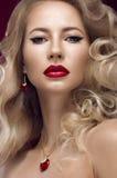 美丽的金发碧眼的女人以与卷毛,红色嘴唇的好莱坞方式 秀丽表面 免版税图库摄影