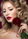 美丽的金发碧眼的女人以与卷毛,红色嘴唇的好莱坞方式 秀丽表面 库存图片