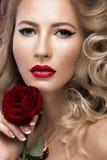 美丽的金发碧眼的女人以与卷毛,红色嘴唇的好莱坞方式 秀丽表面 免版税库存照片