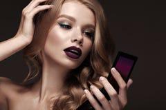 美丽的金发碧眼的女人以与卷毛,黑暗的嘴唇,镜子的好莱坞方式在手中 秀丽表面和头发 库存照片