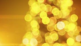 美丽的金黄圣诞树点燃在迷离Bokeh的闪烁的和转动的特写镜头在黄色背景 使成环的3D 股票录像