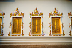美丽的金黄窗口有在泰国tem的白水泥背景 免版税库存照片