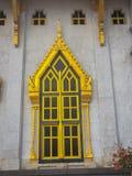 美丽的金黄窗口有在泰国tem的白水泥背景 免版税库存图片
