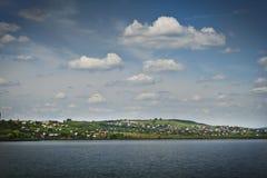 美丽的镇定的风景天空,村庄,湖蓝色 免版税库存图片