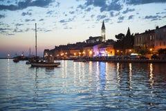 美丽的镇罗维尼夜视图在Istria,克罗地亚 晚上在老克罗地亚城市,与水反射的夜场面 库存照片