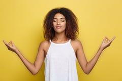 美丽的镇静年轻非裔美国人的黑人女性画象有蓬松卷发发型实践的瑜伽的户内,思考 免版税库存图片