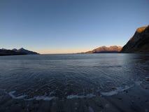 美丽的镇静蓝色在晚秋天挥动击中白色结冰的沙滩在与深山和公海的北极圈 免版税库存照片