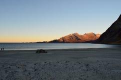 美丽的镇静蓝色在晚秋天挥动击中白色结冰的沙滩在与深山和公海的北极圈 库存照片