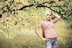 美丽的长发白肤金发的女孩在秋天公园 库存图片