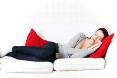 美丽的长沙发休眠的妇女 库存图片