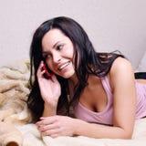 美丽的长沙发愉快的松弛妇女年轻人 库存照片