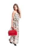 美丽的长的拿着一个红色钱包的头发女性模型 库存图片