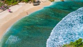 美丽的长的白色波浪和透明的水在Atuh靠岸,努沙Penida,巴厘岛,印度尼西亚 库存图片