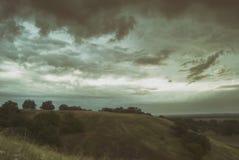 美丽的阴暗阴沉的灰色天空和云彩在多小山谷 免版税库存图片