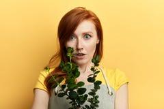 美丽的震惊逗人喜爱的女孩藏品植物和看照相机 免版税库存图片