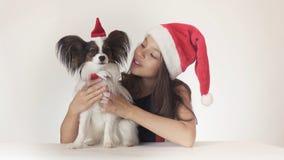 美丽的青少年的女孩和狗大陆玩具西班牙猎狗Papillon在圣诞老人加盖快乐拥抱在白色背景 免版税库存照片