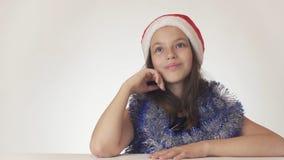 美丽的青少年的女孩在圣诞老人帽子和新年` s闪亮金属片在白色背景愉快地作梦 免版税库存照片