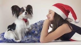 美丽的青少年的女孩在圣诞老人帽子和狗大陆玩具西班牙猎狗在新年使用` s的闪亮金属片的Papillon快乐  免版税库存图片