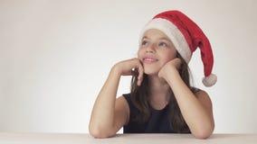 美丽的青少年的女孩在圣诞老人帽子开会和作梦礼物,表达幸福和预期在白色 库存照片