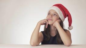 美丽的青少年的女孩在圣诞老人帽子开会和作梦礼物,表达幸福和预期在白色 免版税图库摄影
