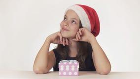 美丽的青少年的女孩在圣诞老人帽子开会和在白色背景做一个愿望 图库摄影