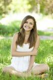 美丽的青少年的女孩在绿草的公园。 免版税图库摄影