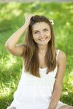 美丽的青少年的女孩在绿草的公园。 免版税库存图片