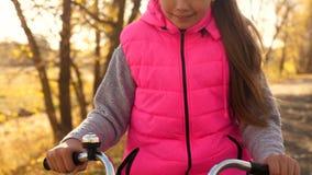 美丽的青少年的女孩在路和笑骑自行车 女孩有长发的和桃红色夹克骑马自行车的在秋天 影视素材