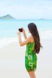美丽的青少年的女孩在拿着照相机的夏威夷拍照片 免版税库存图片