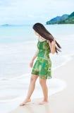 美丽的青少年的女孩在水中的浸洗脚趾在热带海滩 库存图片