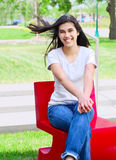 美丽的青少年的女孩户外坐红色椅子 免版税库存照片