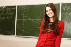 美丽的青少年的女孩高进取者在书桌愉快的s的教室 免版税库存照片