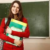 美丽的青少年的女孩高进取者在书桌愉快的s的教室 免版税库存图片