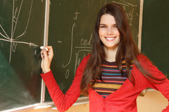 美丽的青少年的女孩高进取者在书桌愉快的s附近的教室 库存照片