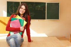 美丽的青少年的女孩高进取者在书桌愉快的s附近的教室 免版税库存图片