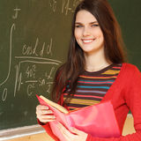 美丽的青少年的女孩高进取者在书桌附近的教室有fo的 免版税库存图片