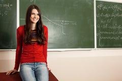 美丽的青少年的女孩高进取者在书桌附近的教室 图库摄影