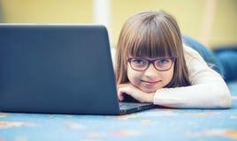 美丽的青春期前的女孩年轻人有片剂膝上型计算机个人计算机的 少年的-青少年孩子教育技术 免版税库存照片